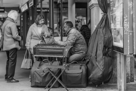 Streetfotografie: Ein Strassenmusiker in Bern unterhält sich mit einer Dame