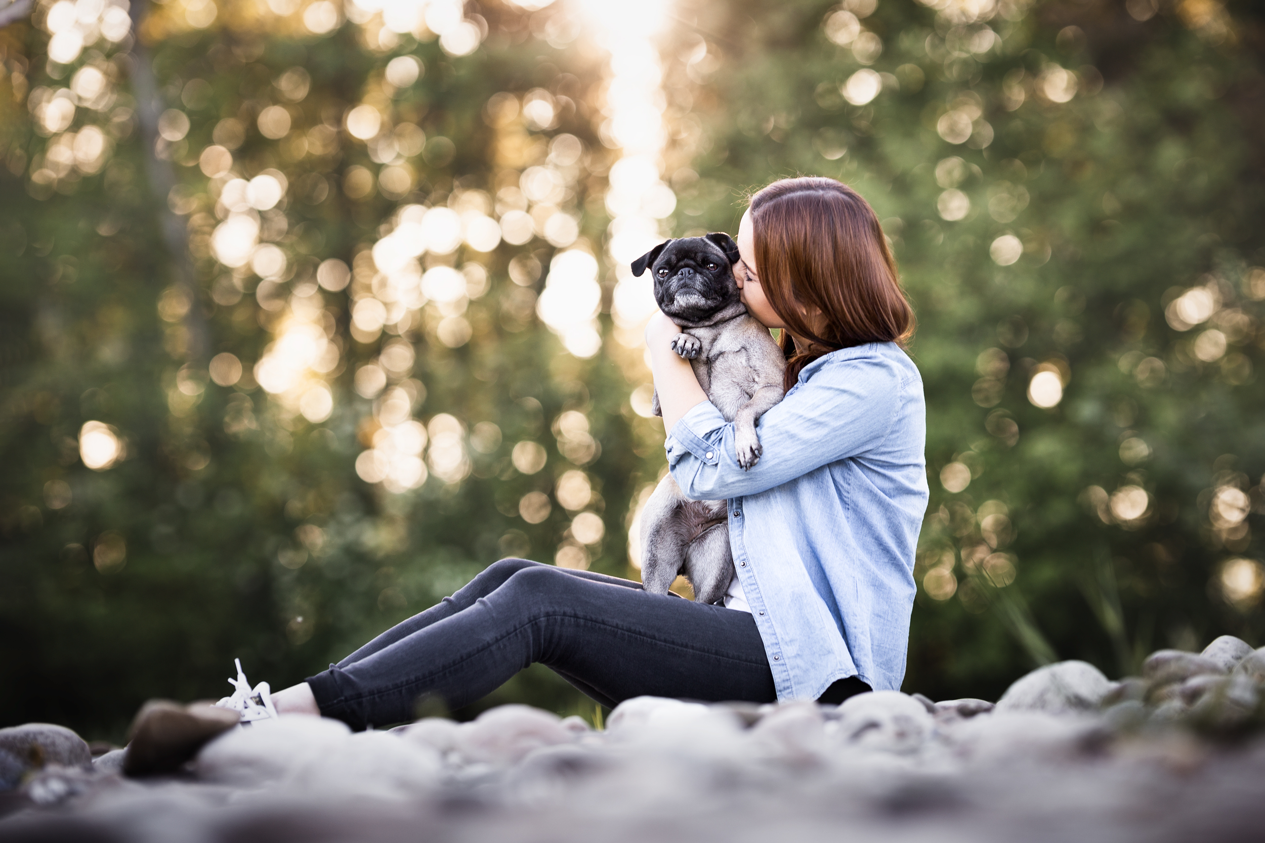 Rebecca und ihre Mopshuendin im Sonnenuntergang an der Aare